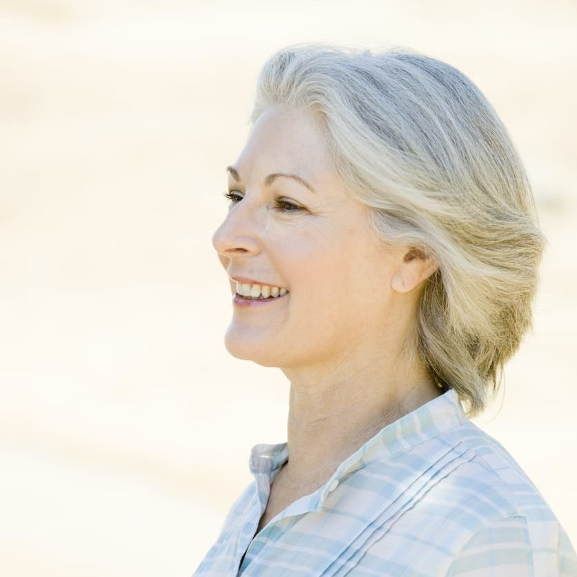 happy older woman with hearing aid device